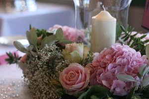 romantic table decoration with pink roses, hydrangea, alstromeria, gypsophila, hebe and eucalyptus